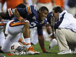 Auburn quarterback Cameron Newton, sporting Under Armour football cleats, speaks with Gene Chizik during warm-ups. 
